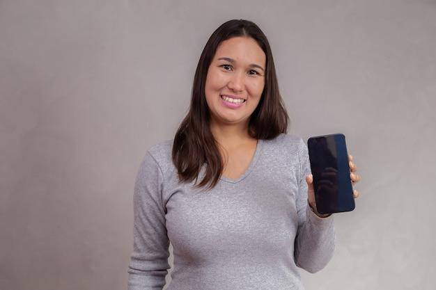 Mulher asiática sorridente está apontando no smartphone em pé sobre um fundo cinza.