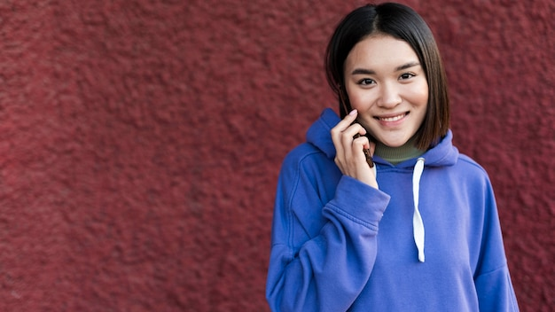 Mulher asiática sorridente falando ao telefone