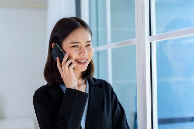 Mulher asiática sorridente falando smartphone no escritório.