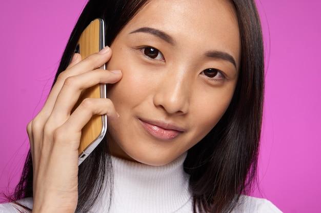 Mulher asiática sorridente, falando sobre o fundo rosa de tecnologia de telefone.