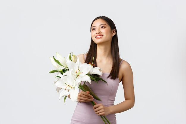 Mulher asiática sorridente feliz em um vestido elegante, olhando no canto superior esquerdo e segurando um buquê de lírios