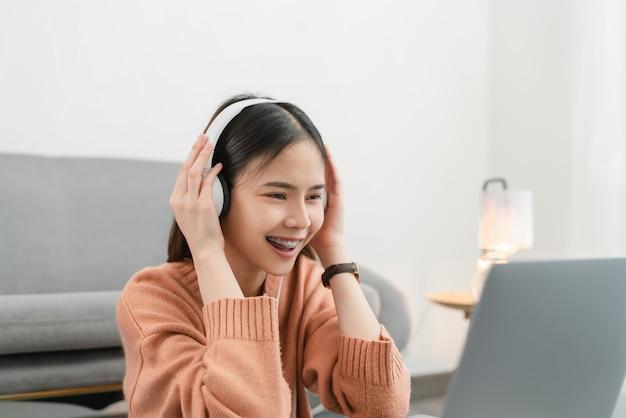 Mulher asiática sorridente feliz ouvindo música de fones de ouvido brancos e usando o laptop de férias em casa.