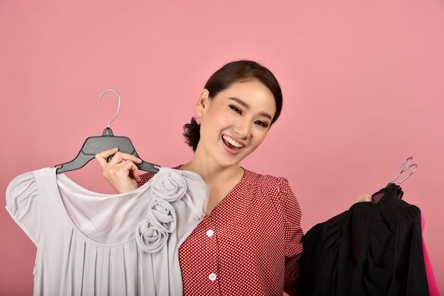 Mulher asiática sorridente gosta de comprar roupas.