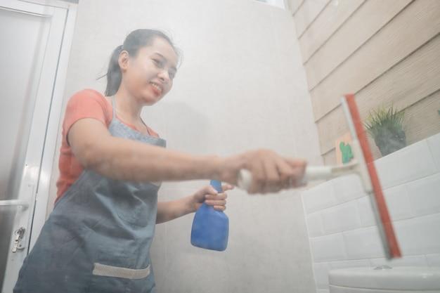 Mulher asiática sorridente limpa a janela usando um limpador de vidros e segura o borrifador enquanto limpa o vidro do vaso sanitário no banheiro