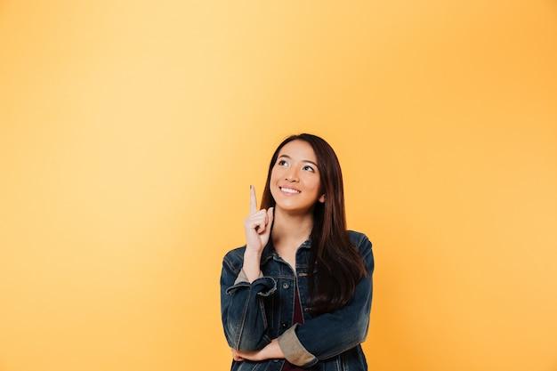 Mulher asiática sorridente na jaqueta jeans, apontando e olhando para cima, sobre fundo amarelo
