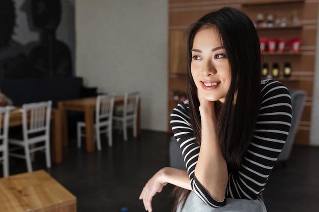 Mulher asiática sorridente pensativa, sentado na cafeteria