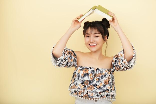 Mulher asiática sorridente posando no estúdio e segurando o livro aberto acima da cabeça