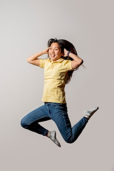 Mulher asiática sorridente pulando no estúdio
