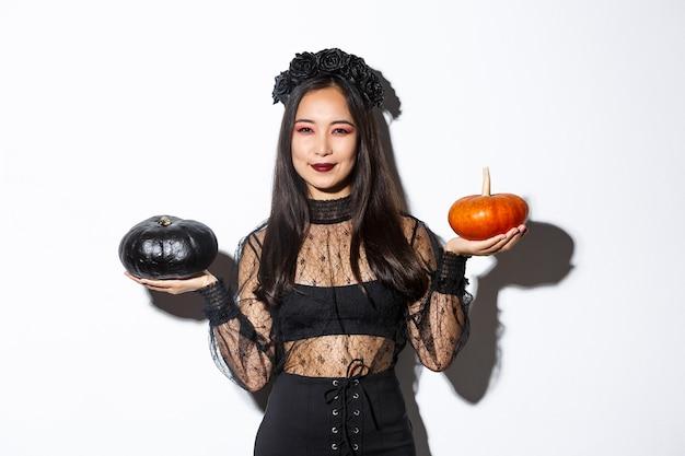 Mulher asiática sorridente, satisfeita, comemorando o dia das bruxas, usando fantasia de bruxa e segurando abóboras