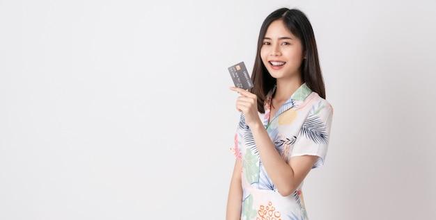 Mulher asiática sorridente segurando o cartão de crédito e olhando para a frente na parede branca com espaço de cópia.