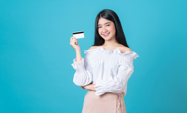 Mulher asiática sorridente segurando pagamento com cartão de crédito