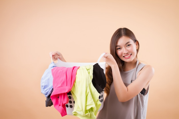 Mulher asiática sorridente segurando um cesto de roupa suja