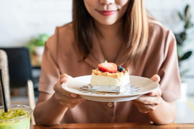 Mulher asiática sorridente segurando um prato de seu bolo de queijo de morango favorito na mesa de madeira no café.