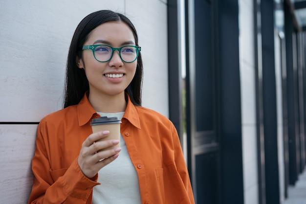 Mulher asiática sorridente segurando uma xícara de café no conceito de pausa para o café na rua