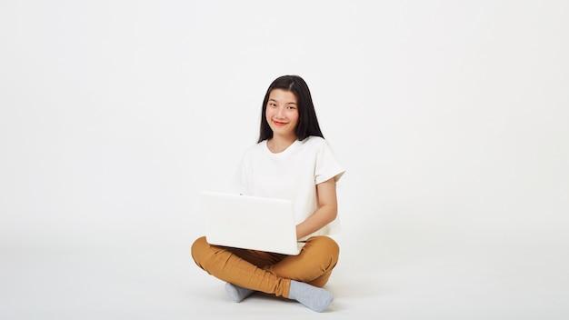 Mulher asiática sorridente trabalhando em um laptop sentado no chão com as pernas cruzadas isoladas sobre fundo branco, conceito de volta à escola
