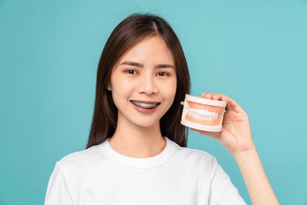 Mulher asiática sorridente usando aparelho, segurando o modelo de dente sobre fundo azul, conceito de higiene bucal e cuidados de saúde.