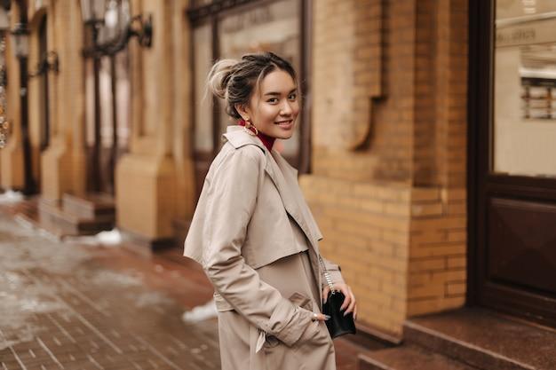 Mulher asiática sorridente, vestida com um casaco bege de outono, segurando uma bolsa crossbody e posando contra um prédio de tijolos.