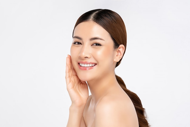 Mulher asiática, sorrindo com a mão, tocando o rosto para conceitos de beleza e cuidados com a pele