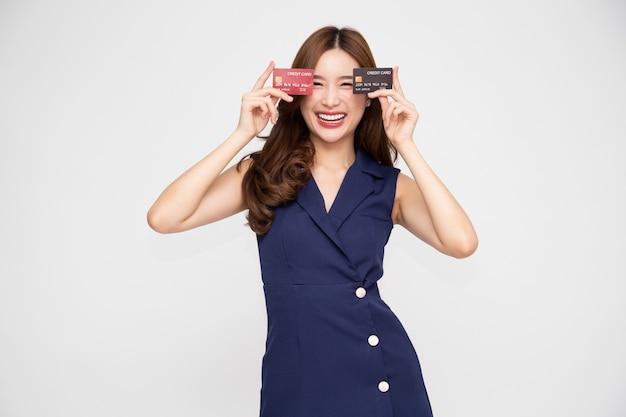 Mulher asiática sorrindo e mostrando cartão de crédito em branco