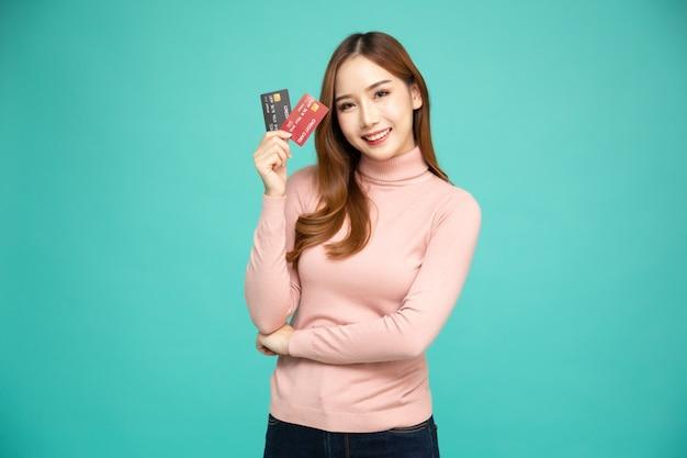 Mulher asiática, sorrindo e mostrando o cartão de crédito.