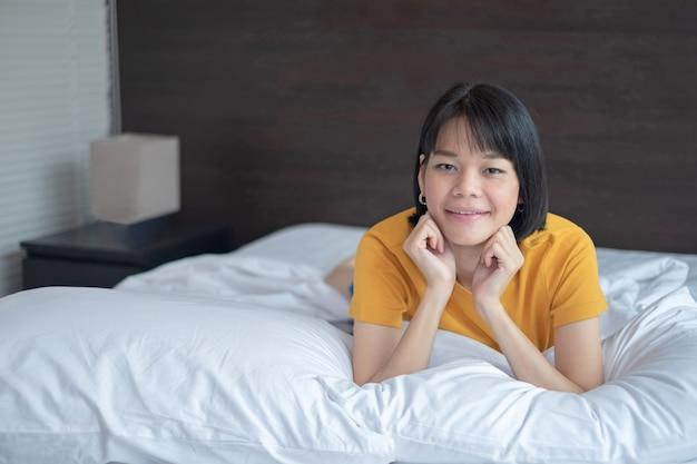 Mulher asiática sorrindo e olhando a câmera na cama branca em casa