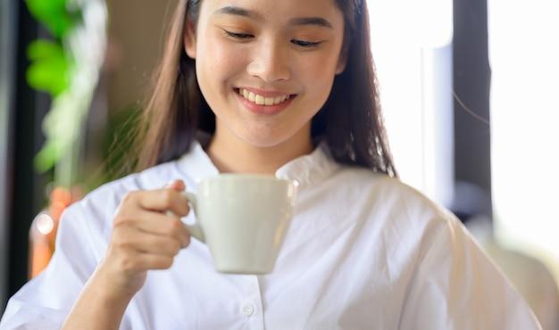 Mulher asiática sorrindo e tomando café no café Foto Premium