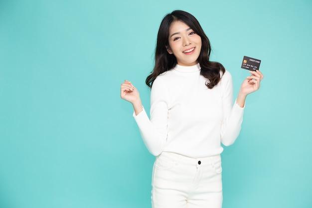 Mulher asiática sorrindo, mostrando o cartão de crédito para fazer pagamento ou pagar negócios online.