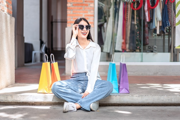 Mulher asiática sorrindo segurando sacolas de compras