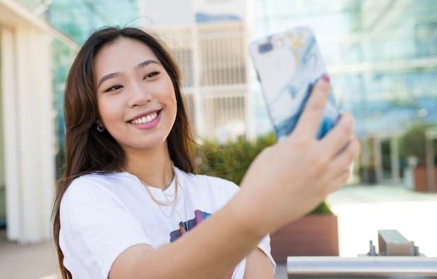 Mulher asiática sorrindo tirando fotos com o celular