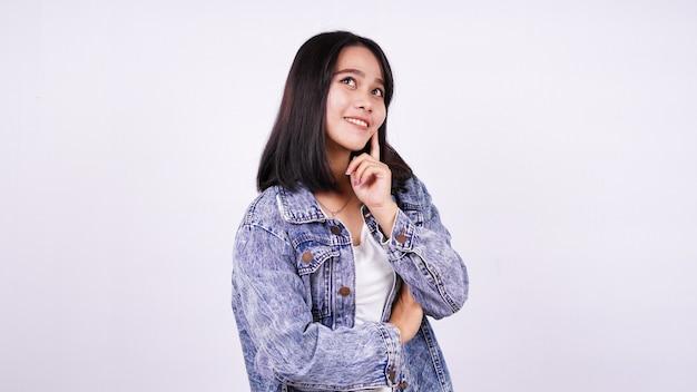 Mulher asiática sorrindo usando jaqueta jeans e pensando em uma ideia com uma superfície branca isolada