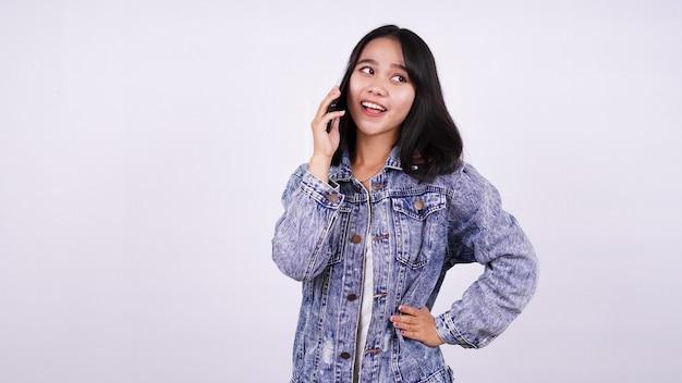 Mulher asiática sorrindo vestindo jaqueta jeans e falando no celular com uma superfície branca isolada