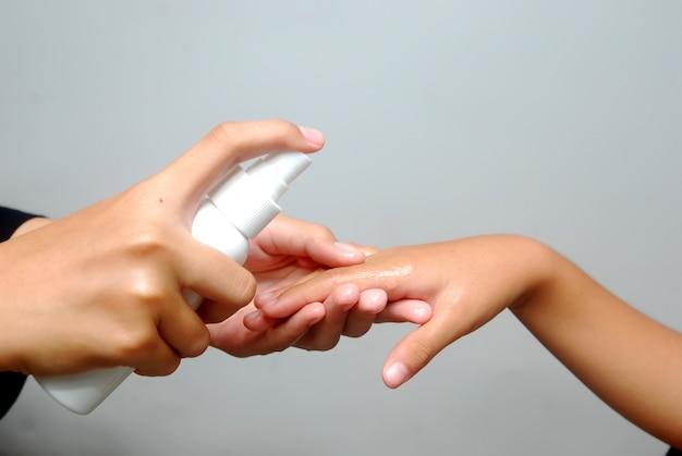 Mulher asiática spray desinfetante para as mãos contra o vírus, bactérias para a mão da criança