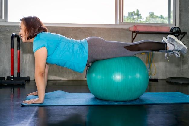 Mulher asiática superior no sportswear que treina os músculos abdominais com gym da bola na aptidão.