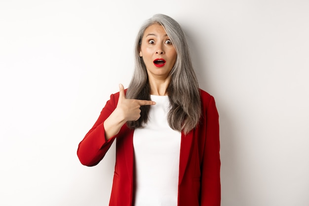 Mulher asiática surpresa com cabelos grisalhos, apontando para si mesma e arfando confusa, em pé sobre um fundo branco