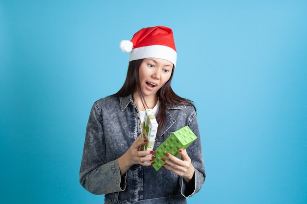 Mulher asiática surpresa com chapéu de papai noel abre presente de ano novo