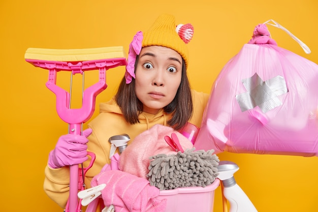 Mulher asiática surpresa e preocupada ajuda os pais a fazerem as tarefas domésticas coleta lixo em saco de polietileno lava chão com esfregão usa diferentes ferramentas de limpeza e detergentes isolados sobre a parede amarela do estúdio