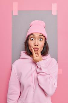Mulher asiática surpresa faz careta, mantém os lábios arredondados, tem olhos esbugalhados, usa chapéu e um capuz parece poses chocadas contra a parede rosa do estúdio com uma folha de papel cinza colada atrás