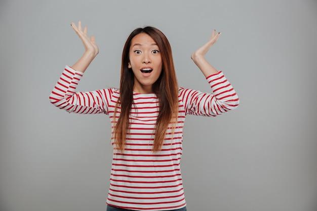 Mulher asiática surpresa na camisola, olhando para a câmera com a boca aberta e mãos para cima, sobre fundo cinza