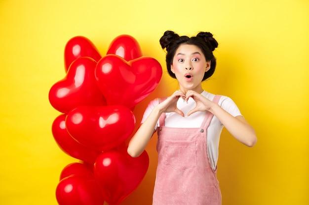 Mulher asiática surpresa olhando maravilhada, mostrando um gesto de coração