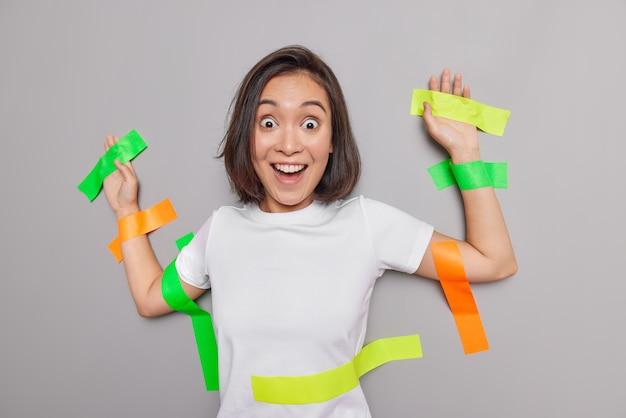 Mulher asiática surpresa positiva colada na parede com fitas adesivas coloridas fica feliz por não poder acreditar seus olhos vestida com uma camiseta branca isolada sobre a parede cinza