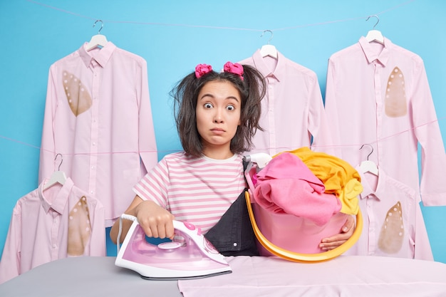 Mulher asiática surpresa que vai passar a ferro na lavanderia segura balde cheio de enorme pilha de roupa lavada usa ferro elétrico chocado para receber mais uma tarefa sobre a casa