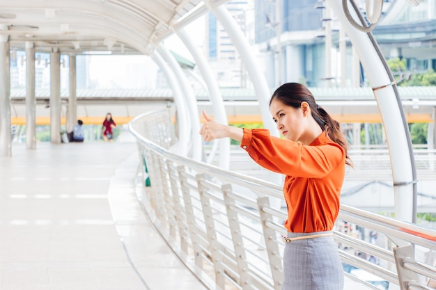 Mulher asiática tailandesa carrancuda e com o polegar para cima