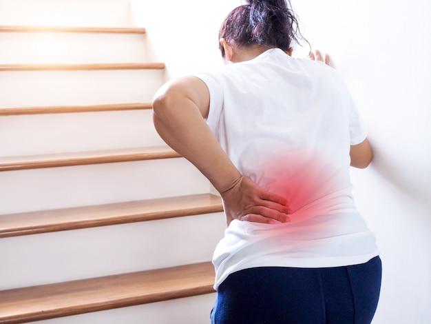 Mulher asiática tailandesa nova que sofre a dor lombar e a dor lombar da cintura ao subir as escadas.