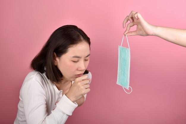 Mulher asiática tem alergia na garganta e tosse, espirros e tosse em local público sem proteção espalhar gotículas de doença por coronavírus (covid-19)