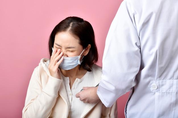 Mulher asiática tem alergia na garganta inflamada e tosse na máscara facial