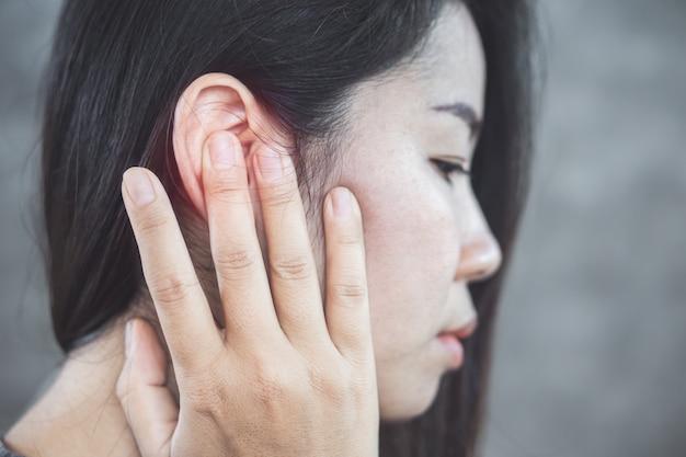 Mulher asiática tem dor no ouvido, conceito de zumbido