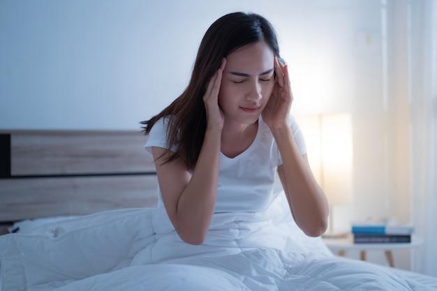 Mulher asiática tem uma dor de cabeça pode ser enxaqueca na parte da manhã na cama