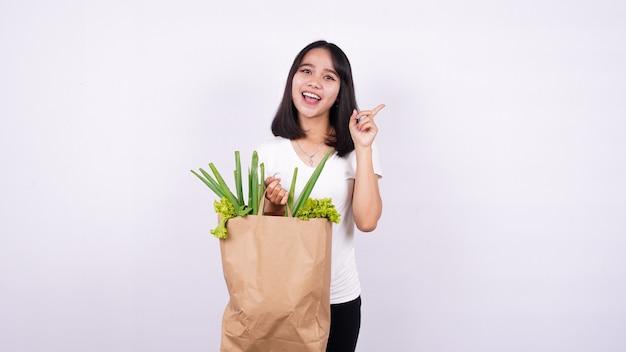 Mulher asiática tem uma ótima ideia com um saco de papel de vegetais frescos com uma superfície branca isolada