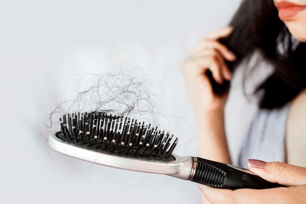 Mulher asiática tendo problema com queda de cabelo