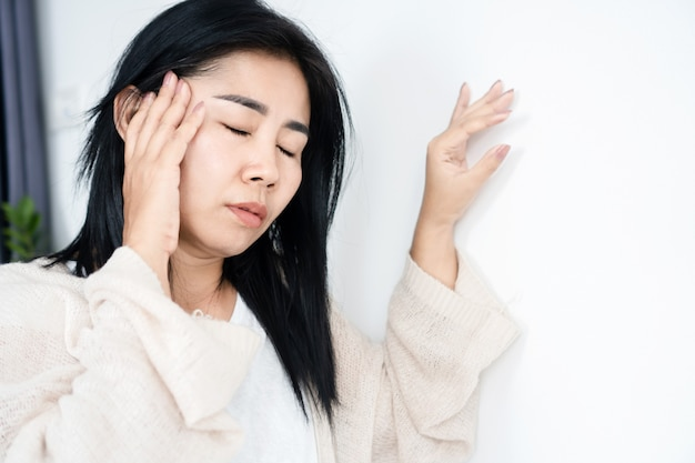 Mulher asiática tendo problemas com a doença de menieres, desmaios ou tonturas, encostada na parede